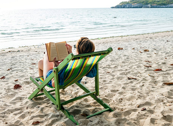 Image of a woman reading a book on a beach